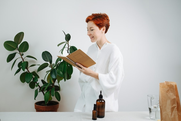 Sorridente donna dai capelli corti che guarda il taccuino ecologico con una copertina di cartone
