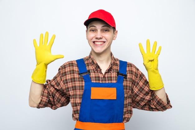 Sorridere mostrando numeri diversi giovane addetto alle pulizie che indossa l'uniforme e il berretto con i guanti