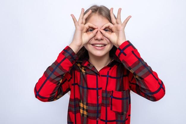 Sorridente che mostra gesto di sguardo bella bambina che indossa una maglietta rossa