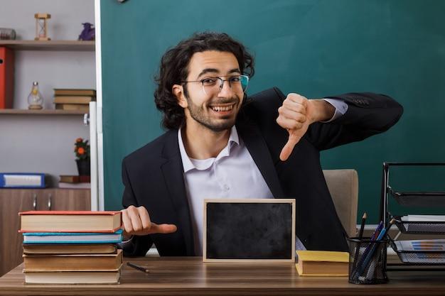 Sorridente che mostra pollice giù insegnante maschio con gli occhiali che tiene mini lavagna seduta al tavolo con gli strumenti della scuola in classe