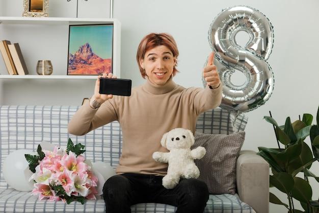 Sorridente che mostra pollice in su bel ragazzo durante la giornata delle donne felici che tiene orsacchiotto con il telefono seduto sul divano nel soggiorno