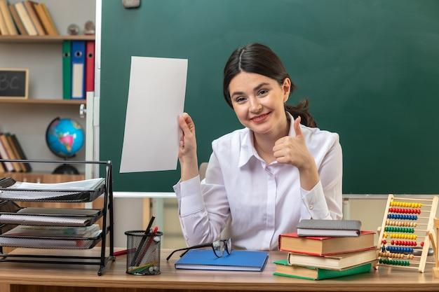 Sorridente che mostra pollice in su giovane insegnante femminile che tiene carta seduta al tavolo con gli strumenti della scuola in aula