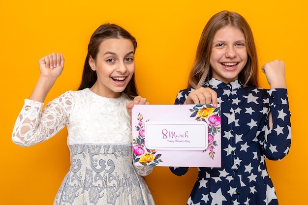 Sorridere mostrando sì gesto due bambine il giorno della donna felice tenendo la cartolina isolata sulla parete arancione