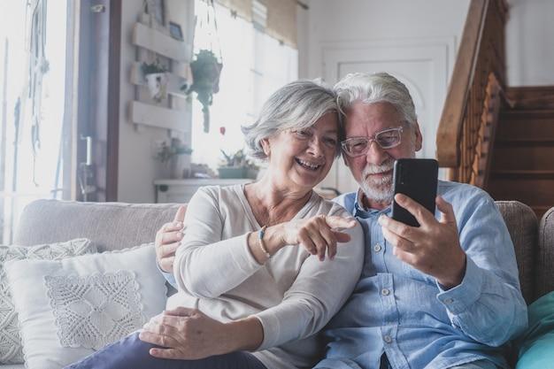 Sorridente coppia di famiglia sposata più anziana matura e sincera che tiene una conversazione di videochiamata mobile con gli amici, godendo della comunicazione a distanza con i bambini cresciuti, utilizzando le applicazioni per smartphone a casa.