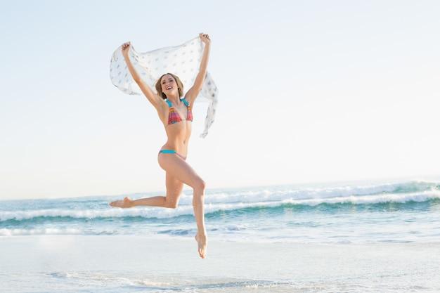 La donna snella sorridente che salta nello scialle della holding dell'aria