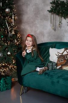 La piccola ragazza sorridente si siede con il regalo sul sofà dall'albero di natale a casa