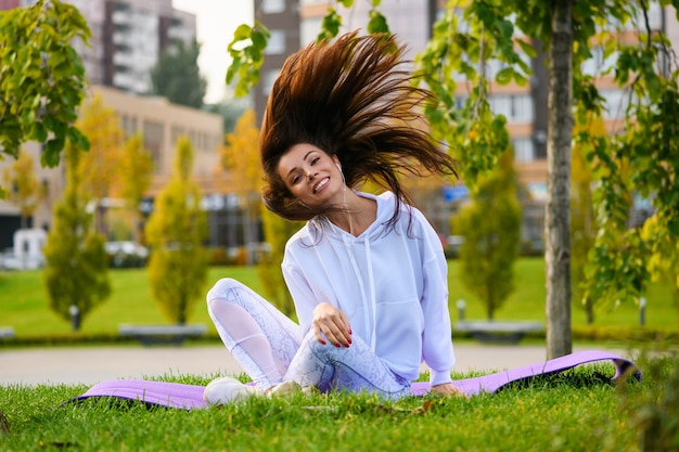 Sorridente ragazza bruna sportiva si siede al tappetino in abiti bianchi, ascolta musica in cuffia con azione sullo sfondo del parco verde della città