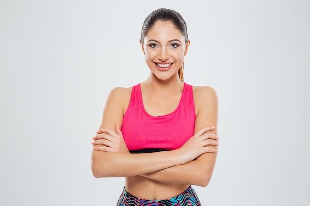 Sorridente donna sportiva in piedi con le braccia conserte e guardando la telecamera