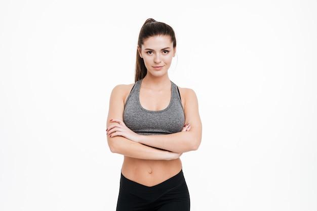 Sorridente donna sportiva in piedi con le braccia conserte e guardando la parte anteriore isolata