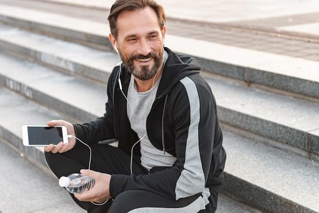 Sportivo sorridente in auricolari utilizzando il telefono cellulare