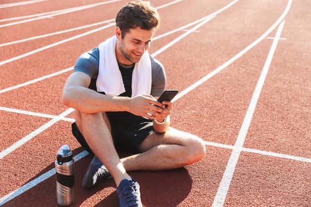 Lo sportivo sorridente ha finito di correre allo stadio, riposando