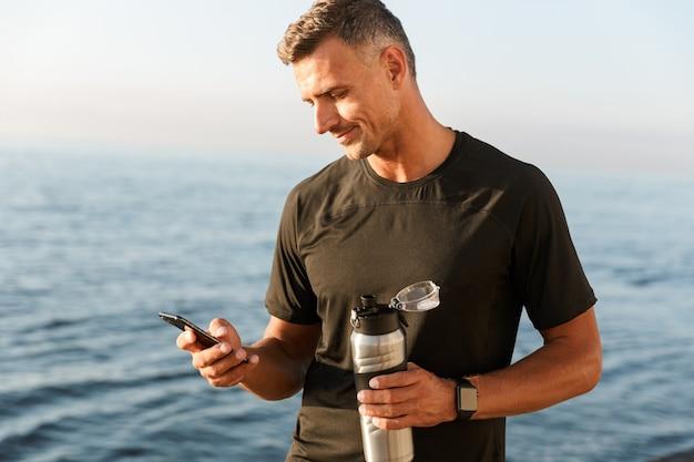 Sportivo sorridente utilizzando il telefono cellulare in piedi
