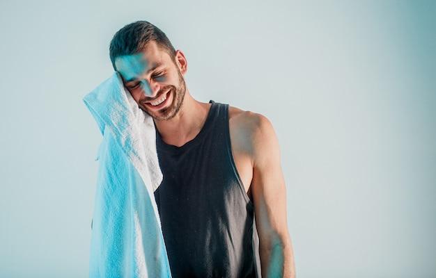 Sportivo sorridente che pulisce con l'asciugamano dopo l'allenamento. il giovane uomo europeo barbuto indossa l'uniforme sportiva. isolato su sfondo grigio con luce turchese. riprese in studio. copia spazio
