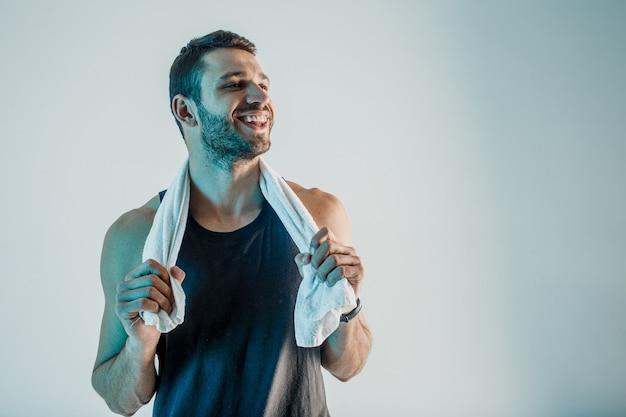 Sportivo sorridente con l'asciugamano. il giovane uomo europeo barbuto indossa l'uniforme sportiva. isolato su sfondo turchese. riprese in studio. copia spazio
