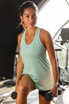 Sportiva sorridente facendo esercizio di fitness con manubri e guardando lontano in palestra