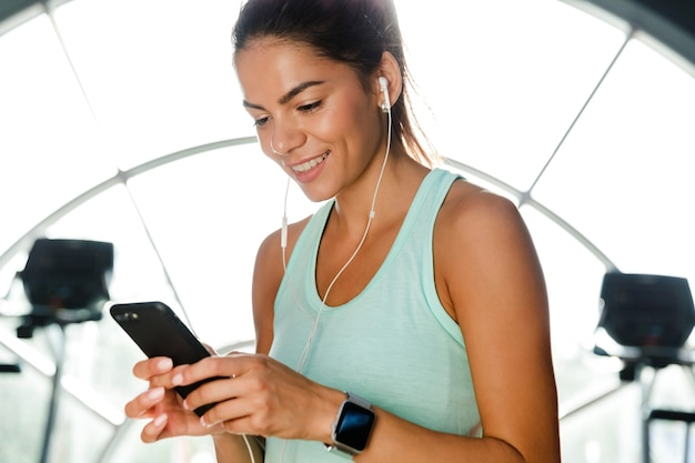 Sportiva sorridente in auricolari ascoltando musica e utilizzando smartphone mentre si è in palestra
