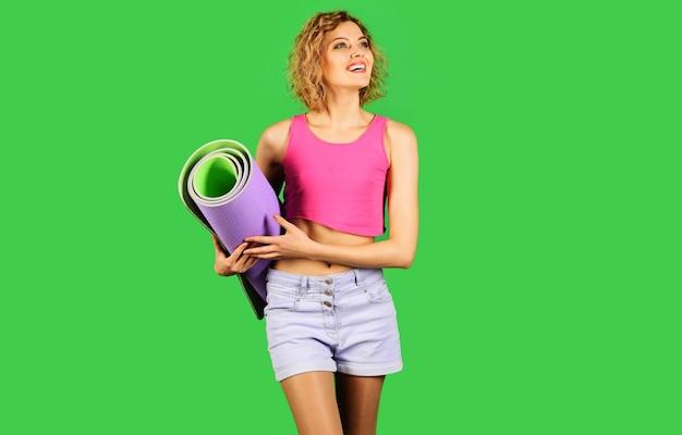 Sportiva sorridente con tappetino fitness. donna adatta con stuoia di yoga. uno stile di vita sano. ragazza sportiva.