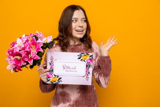 Sorridente mano allargata bella ragazza in felice festa della donna che tiene bouquet con biglietto di auguri