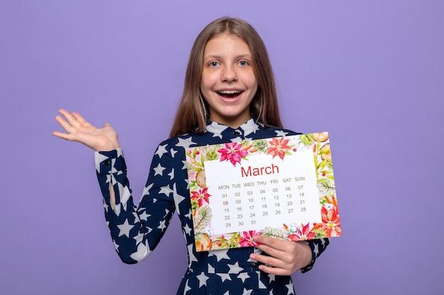 Sorridente allargando le mani bella bambina il giorno delle donne felici che tiene il calendario isolato sulla parete blu