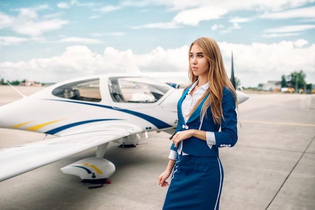 Hostess sorridente in tuta contro il piccolo aeroplano