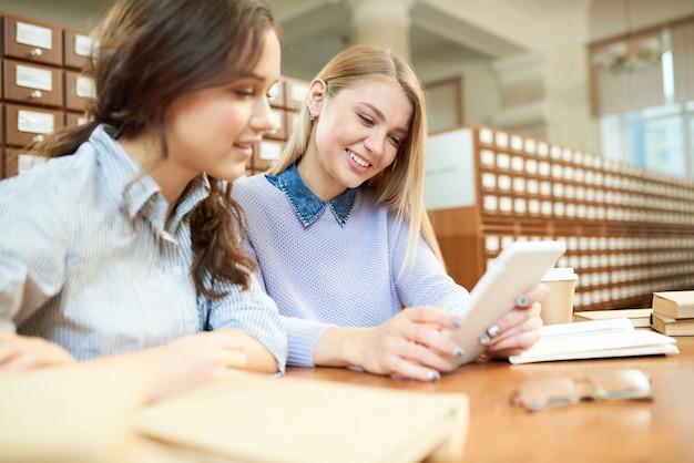 Amici sorridenti dello studente che leggono articolo online in biblioteca