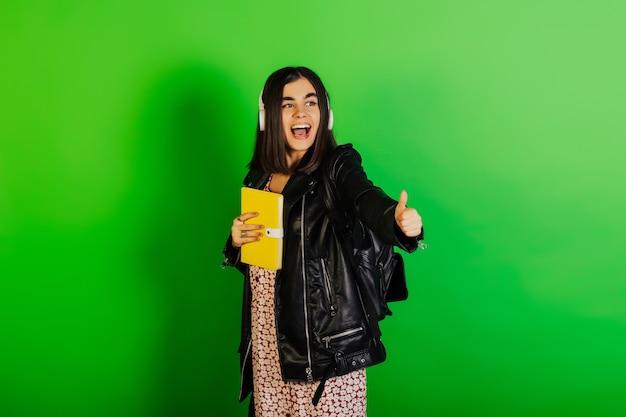 La ragazza sorridente dell'allievo in giacca di pelle nera con lo zaino e le cuffie neri tiene il taccuino giallo e mostra il segno freddo isolato sulla superficie verde.