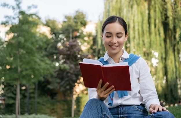 Studente sorridente studiando, imparando la lingua nel parco, leggendo il libro, seduto sull'erba. concetto di educazione
