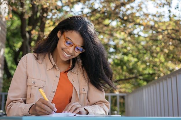 Studente sorridente che studia, apprendimento delle lingue, scrittura, concetto di educazione
