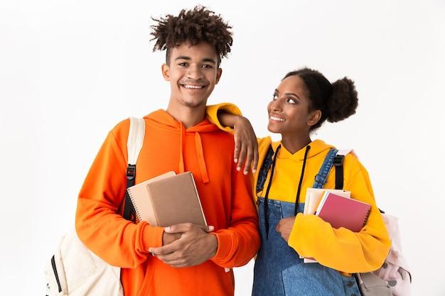 Studenti sorridenti che indossano zaini in possesso di quaderni, isolati su muro bianco