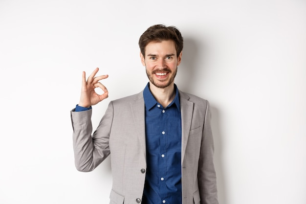 Sorridente imprenditore di successo in tuta che mostra segno ok, guardando soddisfatto