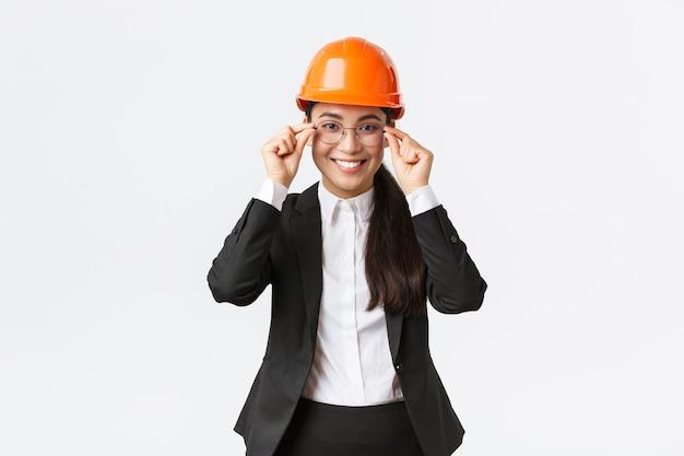 Sorridente imprenditrice di successo in abito nero e casco di sicurezza visita l'area di costruzione per monitorare il lavoro, sorridente soddisfatta, indossa gli occhiali, ingegnere edile che gestisce i lavoratori, sfondo bianco