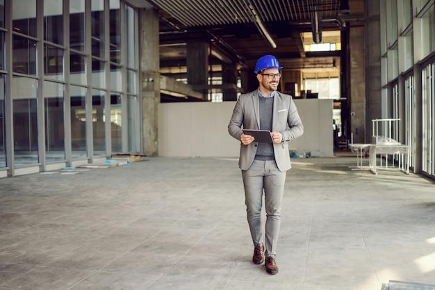 Supervisore sorridente che cammina nell'edificio nel processo di costruzione con il tablet in mano e controlla i lavori.