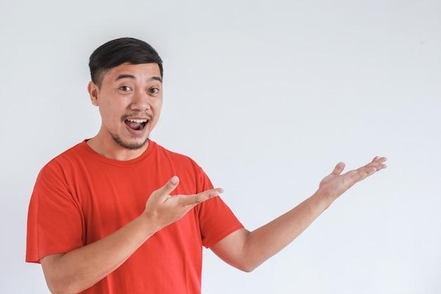 L'espressione del viso sorridente e sorpresa di un uomo asiatico felice in maglietta rossa punta a presentare uno spazio vuoto di contenuto concetto di modello pubblicitario