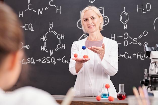 Sorridente insegnante di chimica che presenta un modello di molecola di composto chimico agli scolari contro la lavagna con formula chimica