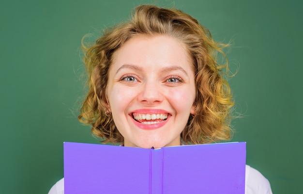 Insegnante sorridente in aula. docente femminile con il libro. argomenti scolastici. formazione scolastica.
