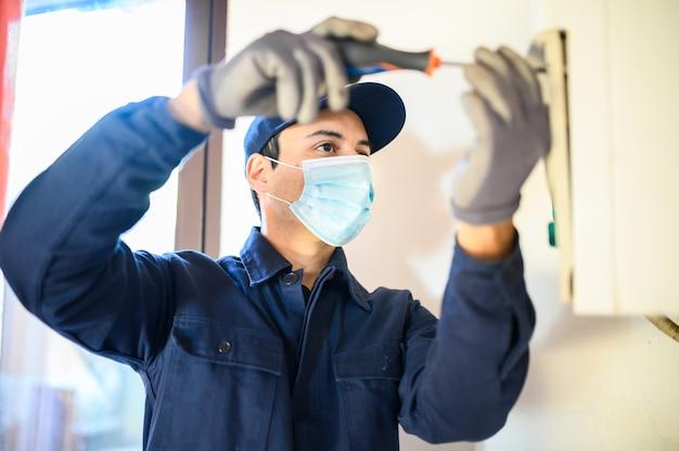 Tecnico sorridente che ripara uno scaldabagno indossando una maschera a causa della pandemia di coronavirus