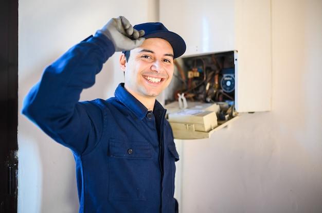 Tecnico sorridente che ripara uno scaldabagno