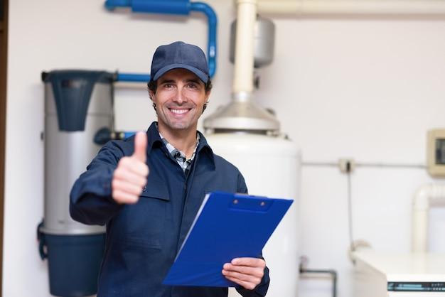 Tecnico sorridente che assiste un riscaldatore di acqua calda