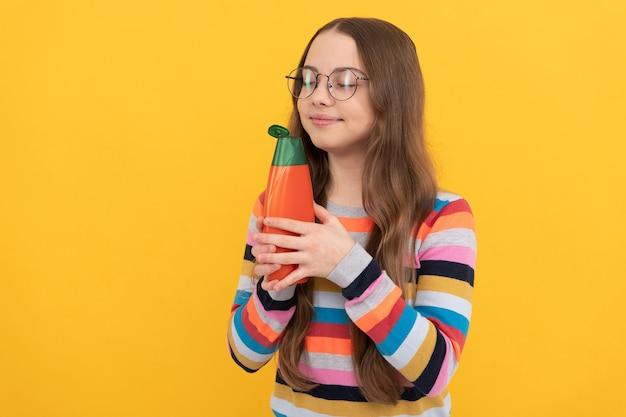 Sorridente ragazza adolescente capelli lunghi in bicchieri odore di shampoo o balsamo per capelli, cura dei capelli.