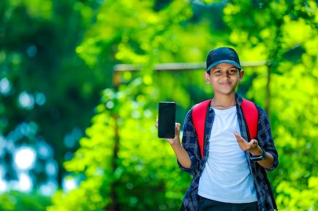 Ragazzo adolescente sorridente in camicia blu che mostra smartphone con lo schermo vuoto