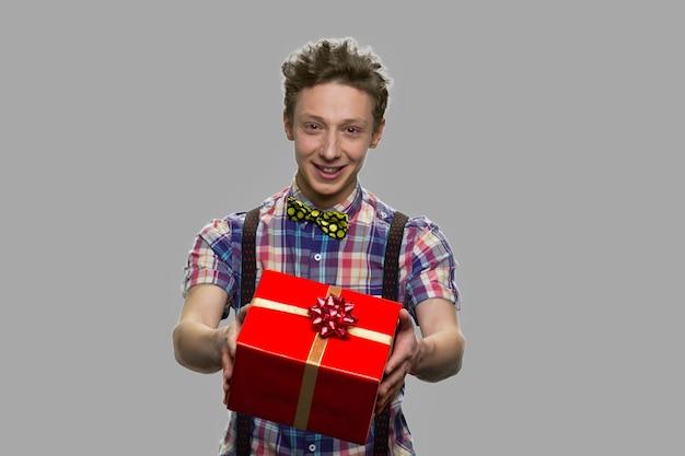 Ragazzo adolescente sorridente che offre confezione regalo. tirante teenager alla moda che dà casella attuale. concetto di consegna di regali.