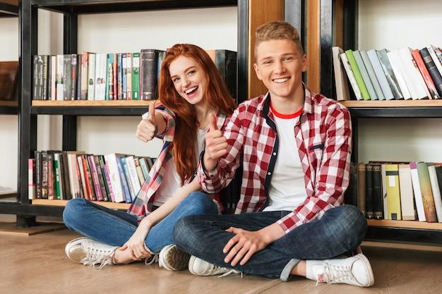 Sorridente coppia adolescente seduto su un pavimento presso lo scaffale per libri