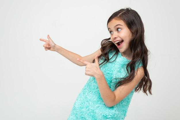 Sorridente ragazza adolescente in un vestito blu punta le mani al lato di uno spazio pubblicitario vuoto su uno sfondo bianco studio.