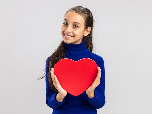 Adolescente sorridente che tiene a forma di cuore guardando la parte anteriore isolata sul muro bianco con spazio di copia