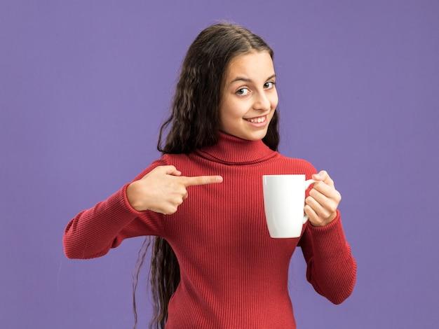 Adolescente sorridente che tiene e che indica alla tazza di tè che esamina macchina fotografica isolata sulla parete porpora