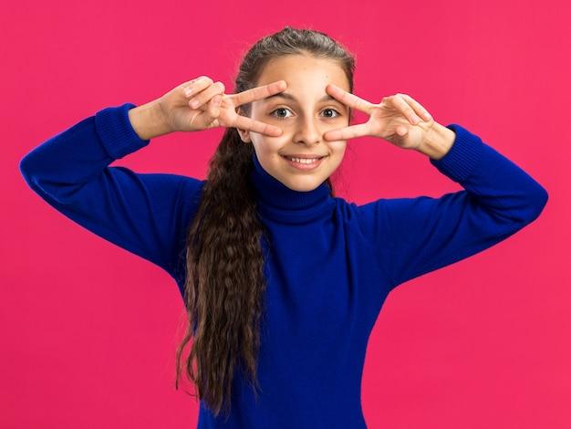 Adolescente sorridente che mostra i simboli del v-segno vicino agli occhi isolati sulla parete rosa