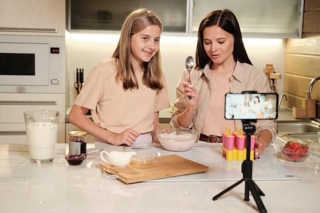 Sorridente ragazza adolescente con ciotola guardando nella fotocamera dello smartphone mentre sua madre con il cucchiaio andando a gustare il gelato fresco fatto in casa