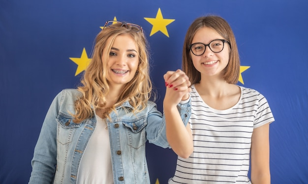 Adolescenti sorridenti si tengono per mano con una bandiera dell'ue dietro di loro.
