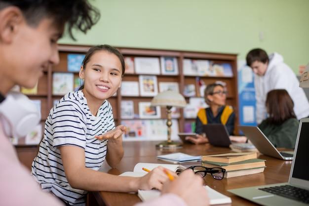 Sorridente studente adolescente condividendo la sua opinione sui punti del progetto mentre prepara il suo piano con un compagno di classe in biblioteca