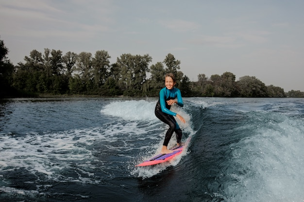 Ragazzo sorridente dell'adolescente che guida sul wakeboard arancione